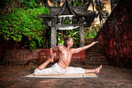 hanuman: Yoga eka pada raja kapotasana by fit man in white trousers near stone temple in tropical forest  Stock Photo
