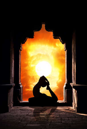hatha: Yoga raja kapotasana pigeon pose by man silhouette in old temple at dramatic sunset sky background. Free space for text