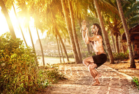 Yoga garudasana eagle pose by fit man with dreadlocks on the beach in Varkala, Kerala, India Stock Photo - 14428595