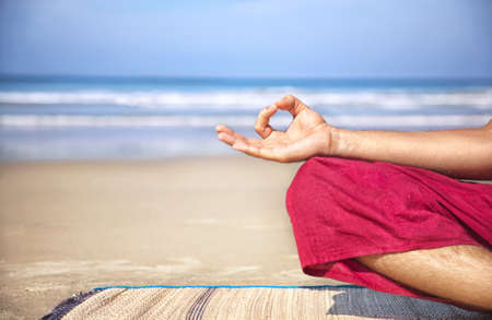 yogi: Meditation mudra of man in red trousers on the beach at ocean background