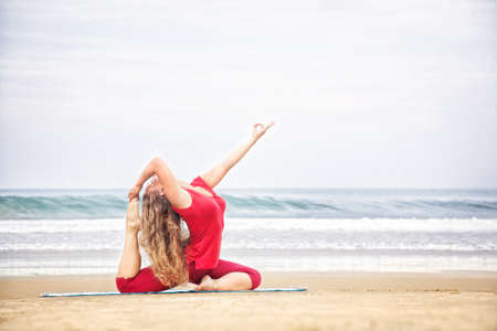 Yoga raja kapotasana dove pose by young woman with long hair in red cloth on the beach at ocean background  photo