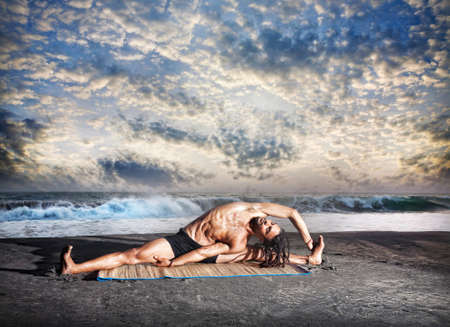indian yoga: Yoga parivrtta janu sirsasana pose by fit man with dreadlocks on the beach near the ocean at sunset background