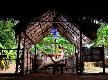 Yoga navasana boat pose by man in white trousers in yoga hall at banana trees background in Varkala, Kerala, India    photo