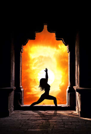 Yoga virabhadrasana I warrior pose by woman silhouette in old temple arch at dramatic sunset sky background. Free space for text photo