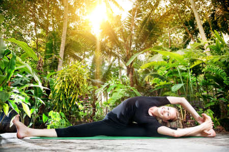 shirshasana: Yoga parivrtta janu sirsasana pose by smiling woman in black cloth in the garden with palms and banana trees