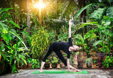 utthita: Yoga utthita trikonasana triangle pose by young woman in black cloth in the garden with palms and banana trees Stock Photo