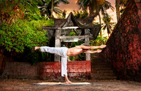 Yoga virabhadrasana warrior III pose by man in white trousers near stone temple at sunset background in tropical forest  photo