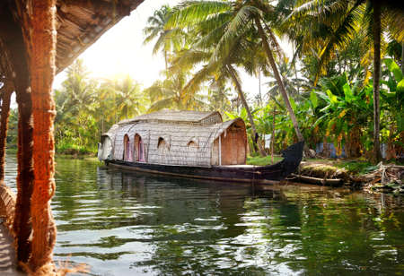 kerala culture: House boat in backwaters at palms background in alappuzha, Kerala, India
