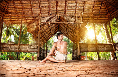 Yoga matsyendrasana twisting pose by fit man in white trousers on the drought earth in yoga shala, Varkala, Kerala, India photo
