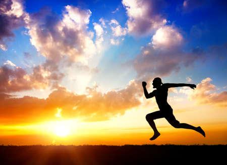 曇っている背景には太陽に向かって走っている男のシルエット 写真素材