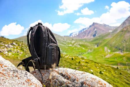 Černý batoh na kameni v horách v Kazachstánu, Střední Asii