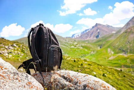 Black backpack on the stone in mountains in Kazakhstan, central Asia Stock Photo