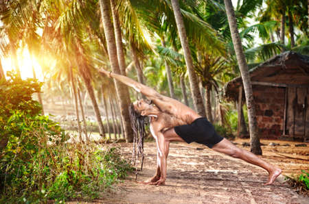 Yoga Parivrtta Parsvakonasana horizon pose by fit man with dreadlocks on the beach near the fishermen hut in Varkala, Kerala, India photo