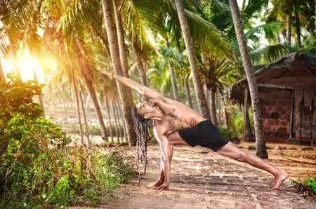 Yoga Parivrtta Parsvakonasana horizon pose by fit man with dreadlocks on the beach near the fishermen hut in Varkala, Kerala, India Stock Photo - 14625044