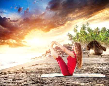 Yoga naukasana boat pose by young woman with long hair on the beach near the ocean at dramatic sunset background Stock Photo - 14625043