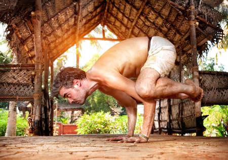 hatha: Yoga bakasana crane pose by fit man in white trousers on the drought earth in yoga shala, Varkala, Kerala, India Stock Photo