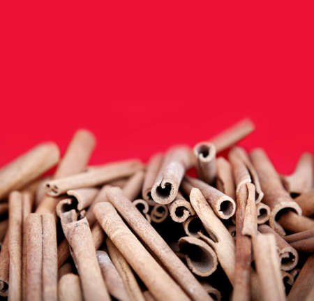 Cinnamon spice heap on red background.   Stock Photo - 14623843