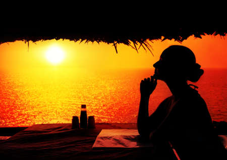 Young woman in restaurant waiting for dinner in Varkala, Kerala, India photo