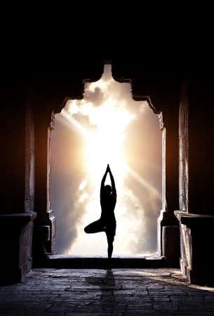 paz interior: Yoga Vrikshasana actitud del árbol de la silueta del hombre en el arco del templo antiguo en el fondo dramático cielo del atardecer. Espacio libre para el texto