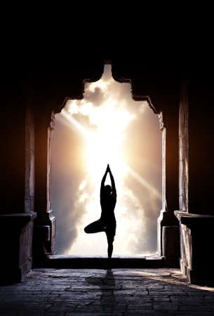 inner peace: Yoga vrikshasana tree pose by man silhouette in old temple arch at dramatic sunset sky background. Free space for text