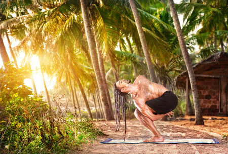 baddha: Yoga twisted pose by fit man with dreadlocks on the beach near the fishermen hut in Varkala, Kerala, India
