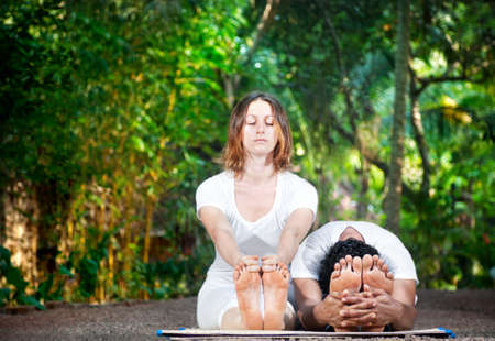 bending forward: Yoga couple of man and woman in white cloth doing paschimottanasana forward bending in the garden Stock Photo