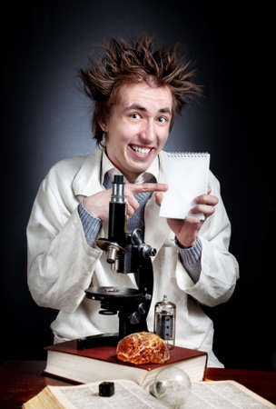 madman: Funny young professor in white coat with microscope pointing at white blank notebook  Stock Photo