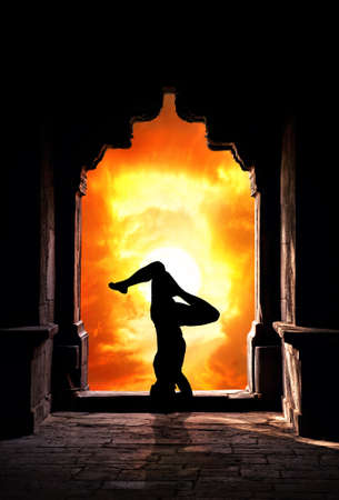 Yoga sirsasana headstand pose by man silhouette in old temple at dramatic sunset sky background. Free space for text photo