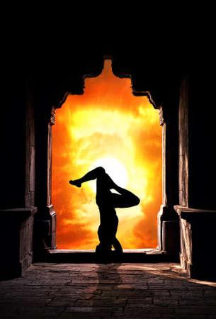 paz interior: Yoga sirsasana parada de cabeza plantean por la silueta del hombre en el antiguo templo en el fondo dramático cielo del atardecer. Espacio libre para el texto Foto de archivo
