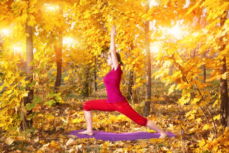 hatha: Yoga virabhadrasana warrior pose by beautiful woman in red cloth and yellow leaves around in the autumn