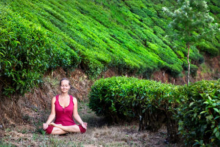 dhyana: Yoga meditation in padmasana lotus pose by woman in red cloth on tea plantations in Munnar hills, Kerala, India Stock Photo
