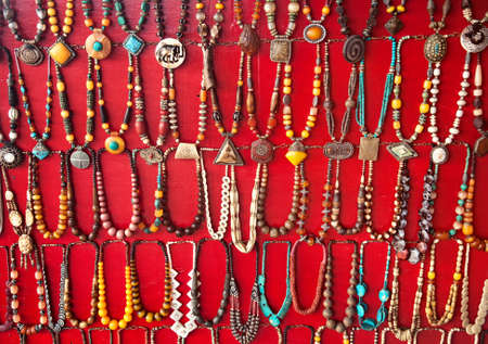 Various colorful Necklaces on red background at flea market in India