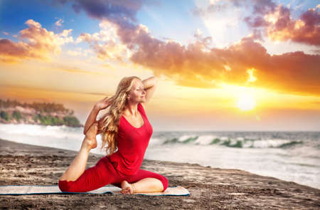 Yoga raja kapotasana pigeon pose by young woman with long hair in red cloth on the beach near the ocean at dramatic sunset background  photo