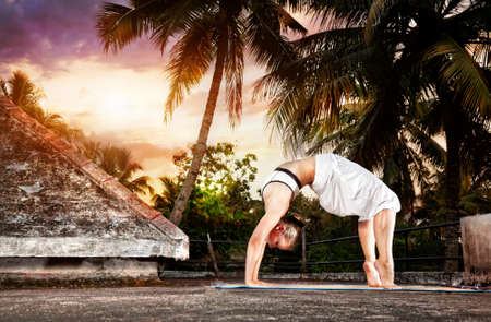 Yoga urdhva dhanurasana pose by woman in white cloth on the roof at palm trees and sunset background in Varkala, Kerala, India photo