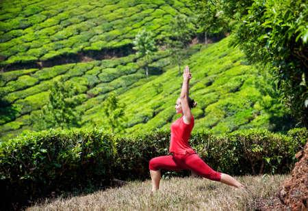 virabhadrasana: Yoga virabhadrasana I warrior pose by woman in red cloth on tea plantations in Munnar hills, Kerala, India