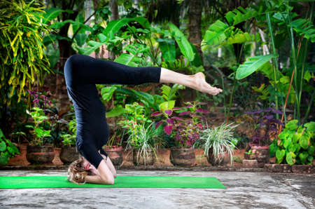 Yoga shirshasana headstand pose by young woman in black costume in the garden with banana trees and tropical plants in the pots photo