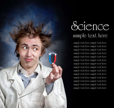 Funny young professor in white coat holding magnet with electricity lighting. Free space for your text photo