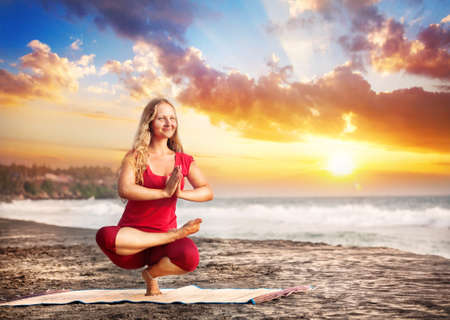 Yoga balancing pose by young woman with long hair in red cloth on the beach near the ocean at dramatic sunset background  Stock Photo
