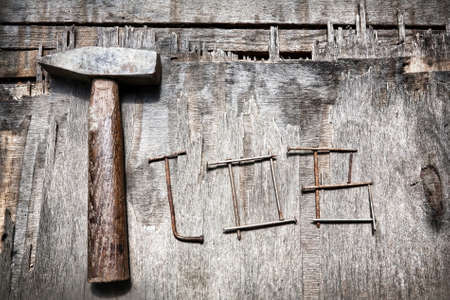 rusty nail: Job word from nails and old hammer on the textured wooded background