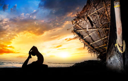 animal practice: Silueta de hombre que hace la paloma la inclinaci�n hacia atr�s posan en la playa cerca del barco de pescadores en el atardecer de fondo en la India Foto de archivo