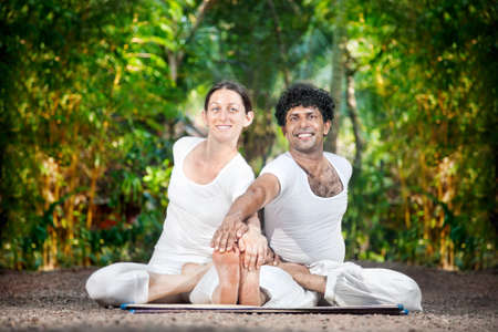 Couple Yoga of man and woman in white costumes doing ardha baddha paschimottanasana, looking at camera and smiling in the garden in Kerala, India photo