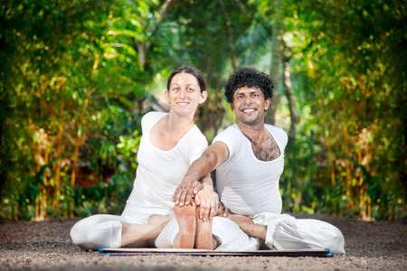 position d amour: Yoga Couple de l'homme et la femme dans des costumes blancs font ardha baddha Paschimottanasana, regardant la cam�ra et souriant dans le jardin dans le Kerala, en Inde