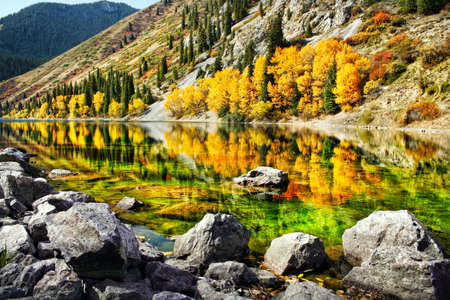 Kolsai mountain lake with yellow trees and reflection in autumn in Kazakhstan, central Asia photo