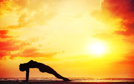 plank position: Yoga purvottasana upward plank pose by beautiful woman on the beach near the ocean at dramatic sunset background  Stock Photo