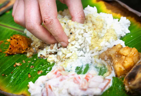 Man eating Indian traditional vegetarian thali from rice, dal, potatoes, tomato salad on banana leaf in restaurant    Stock Photo