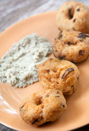 Indian traditional breakfast vada with coconut chutney on orange plate in restaurant    photo