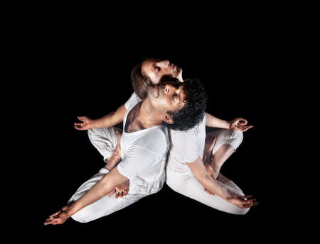 dhyana: Couple Yoga meditation of man and woman in white cloth doing padmasana lotus pose with closed eyes isolated on black background