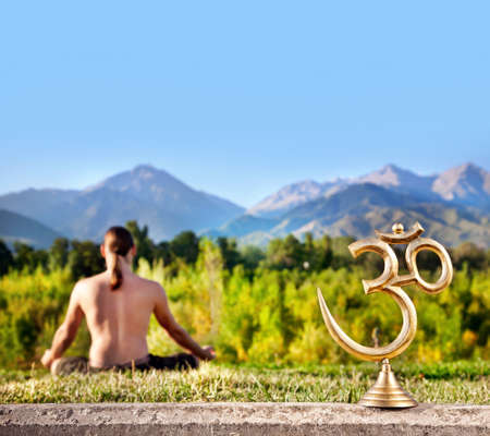 spiritual journey: Om statue and man doing meditation at mountain background. Free space for text
