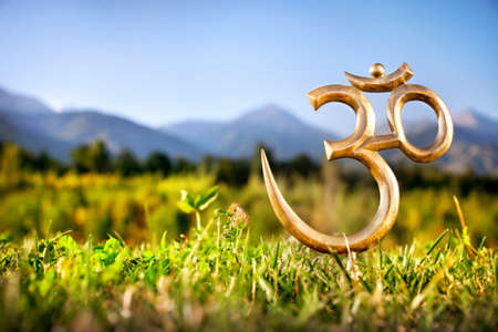 Om statue on the grass at mountain background. Free space for text Stock Photo