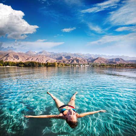 여자 키르기스스탄, 중앙 아시아에서 산 배경에 Issyk 쿨 호수에있는 별처럼 누워
